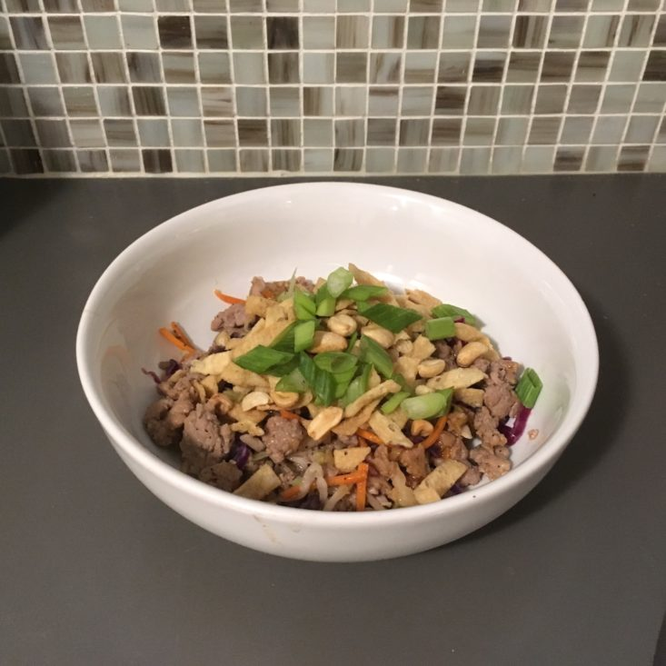 completed egg roll in a bowl recipe in a large white bowl white green onion and peanut garnish